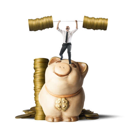capitalism: Concept of earning of a businessman who raises money as weights Stock Photo