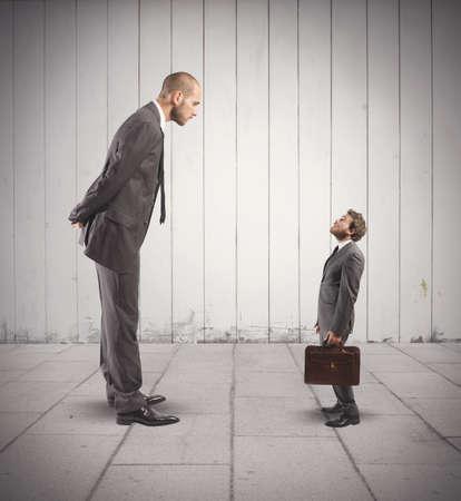 discutere: Concetto di business concorrenza con grandi e piccoli uomini d'affari Archivio Fotografico