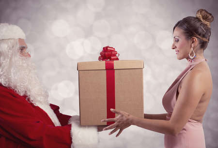 delivers: Santa Claus delivers the gift to a girl Stock Photo