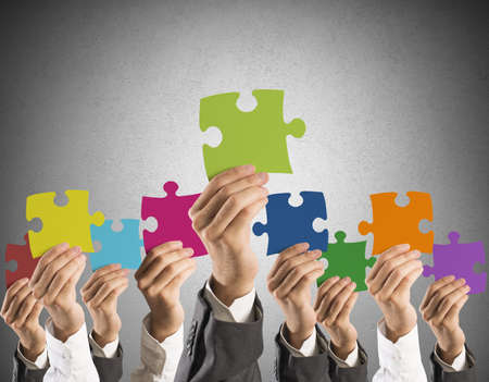 merging: Concept of teamwork and integration with businessman holding colorful puzzle Stock Photo