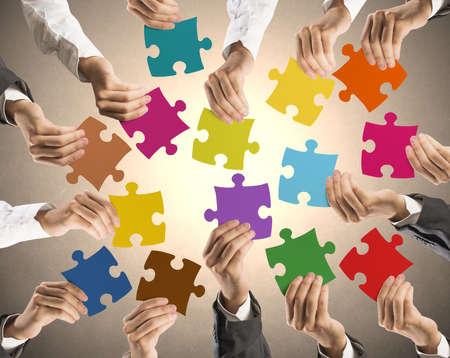 チームワークとカラフルなパズルを保持しているビジネスマンとの統合の概念