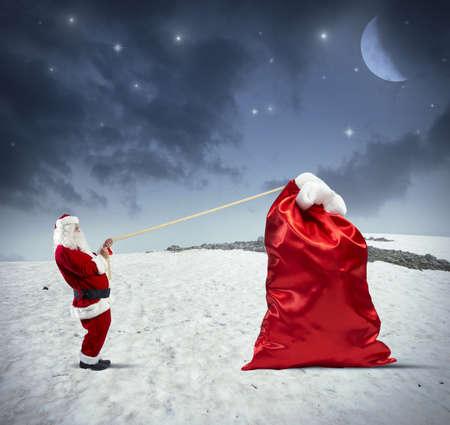 sacks: Santa claus pulls heavy bag of gifts Stock Photo