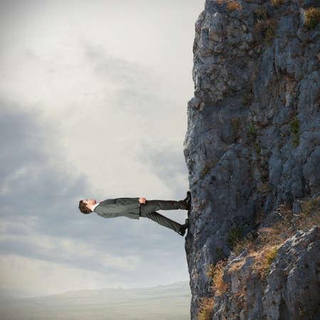 勇敢なビジネスマンが山を越え垂直方向に歩く