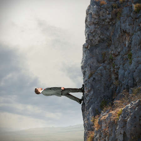 Brave businessman walks vertically over the mountain photo