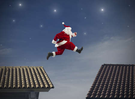 Fast Santa Claus jumping on a roof Stock Photo