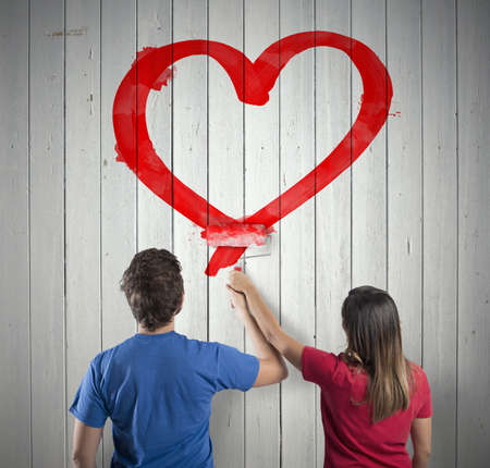 pareja en casa: Pareja joven que drena un coraz�n rojo grande
