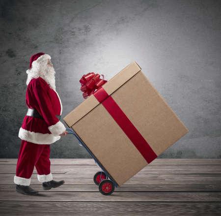 generosidad: Santa Claus con un gran regalo de Navidad en una cesta