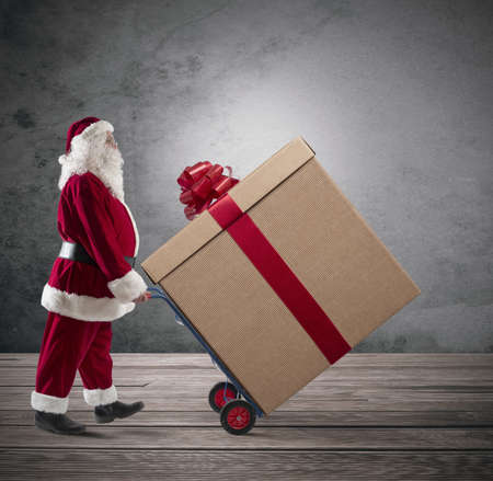 Santa Claus with big Christmas present in a cart photo