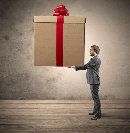 gifts: Elegante zakenman die een groot kerstcadeau Stockfoto