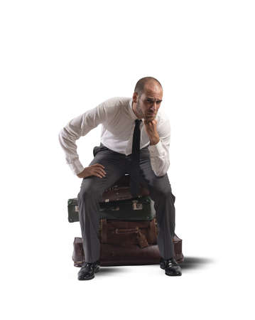 road worker: Concept of lost businessman confused sitting on suitcases Stock Photo