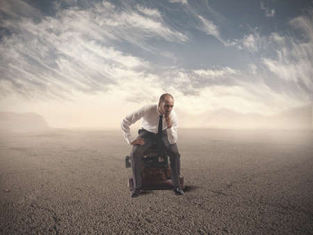 Concept of lost businessman confused sitting on suitcases Stock Photo - 23373219