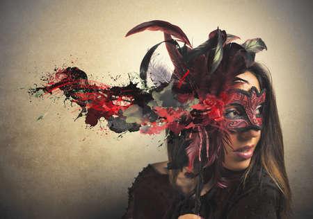 赤と黒のカーニバルのマスクを持つ美しい女性