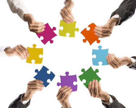 merging together: Concept of teamwork and integration with businessman holding colorful puzzle Stock Photo