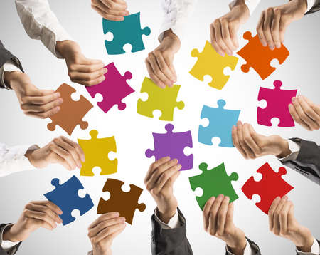 associations: Concept of teamwork and integration with businessman holding colorful puzzle Stock Photo