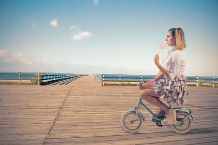 Concept of summer fashion with girl on the bike photo