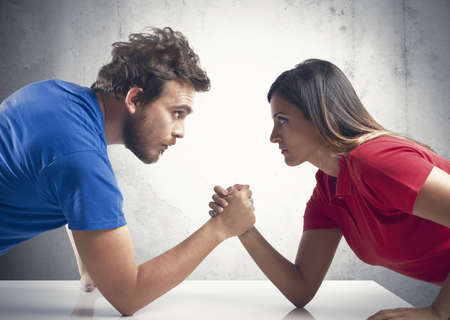 Arm wrestling challenge between a young couple photo