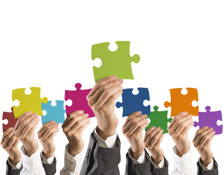 Concept of teamwork and integration with businessman holding colorful puzzle photo
