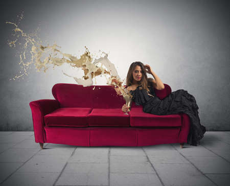Beautiful girl drinking wine on a red sofa Stock Photo - 23529563