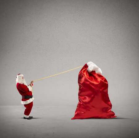 Santa claus pulls heavy bag of gifts photo