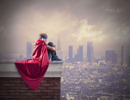 Superhero kid sitting on a wall that controls the city Stock Photo