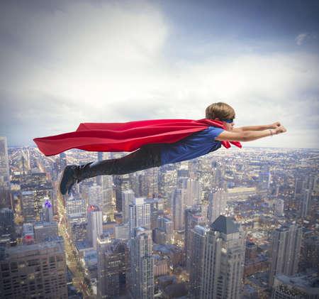 高速都市上空を飛行のスーパー ヒーローの子供