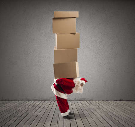 Santa Claus carrying on his back many gifts photo
