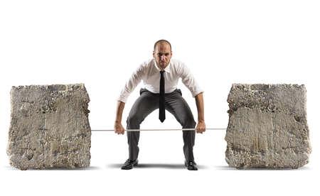 Atleet zakenman met barbell en zware stenen