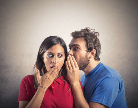 secret information: Concept of gossip with boy whispers girl Stock Photo