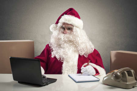 Santa Claus working with laptop in a office photo