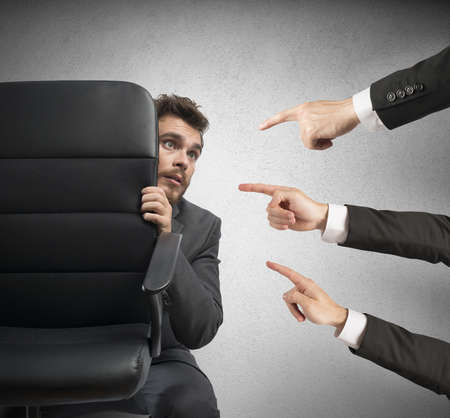 accusation: Concept of businessman culprit behind a chair Stock Photo