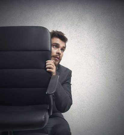 hidden: Concept of fear of a businessman behind a chair Stock Photo