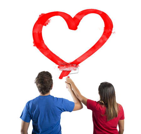 Young couple drawing a big red heart photo