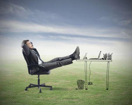 Succesvolle zakenman ontspannen in een denkbeeldige kantoor Stockfoto