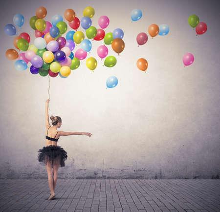 カラフルな風船と踊る美しい少女 写真素材