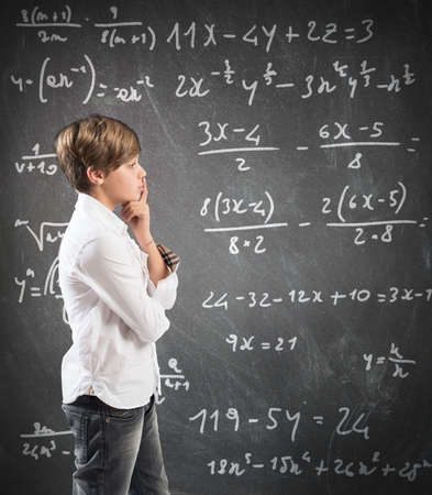 Thinking child with mathematical problem in the blackboard photo