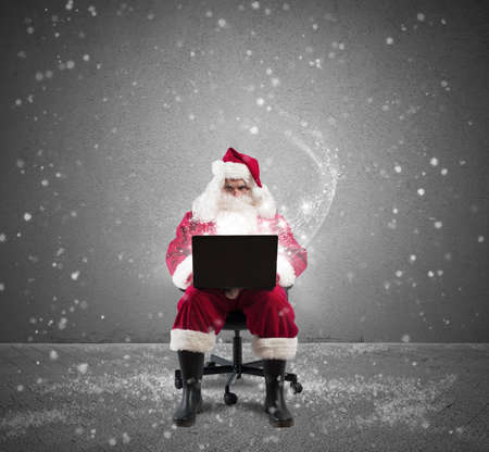 Santa Claus with laptop with snow and star Stock Photo - 24140649