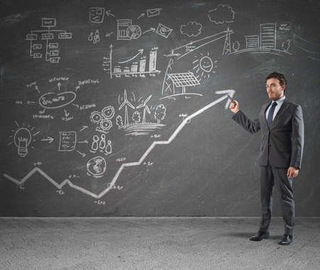 creative concept: Businessman drawing strategy in a blackboard