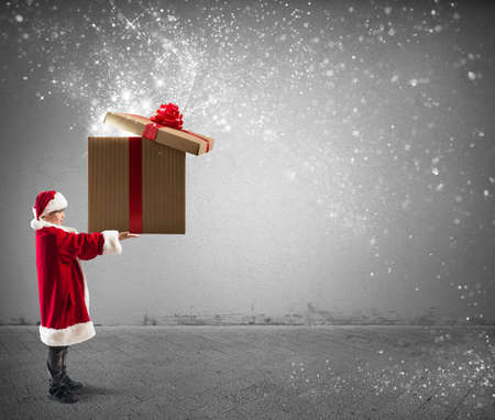 Litte Santa Claus holding a big Christmas present with magic effect photo