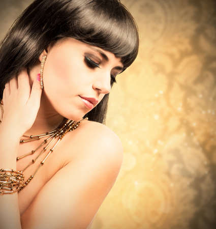 Golden fashion with beautiful brunette young woman photo
