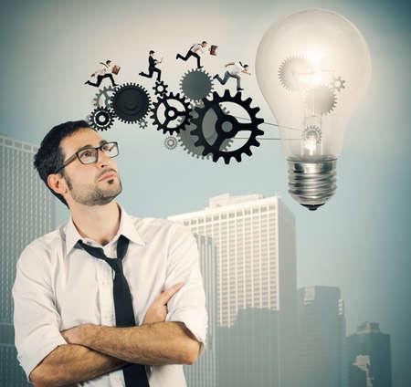 Businessman powering a big idea with a gear system photo