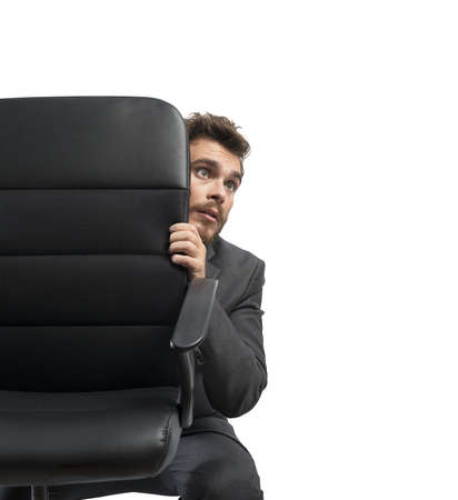 face guard: Concept of fear of a businessman behind a chair Stock Photo