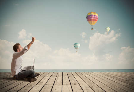 hot air balloon: Successful businessman working outdoor with a laptop Stock Photo