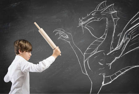 psicologia infantil: Concepto de ni�o valiente, con dibujo de drag�n Foto de archivo