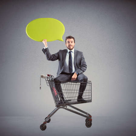 Big message of a businessman with shopping cart photo