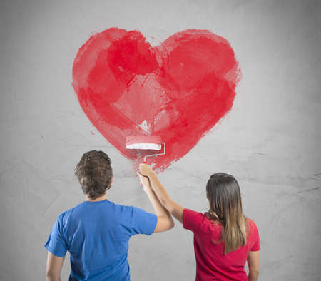 Young couple drawing a big heart in a wall photo