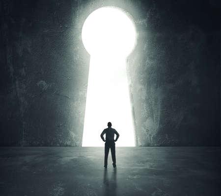 Concepto de éxito con el empresario mirando a través del orificio de la llave