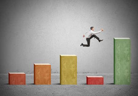 crisis economica: El hombre de negocios salta a la crisis con un salto en una estadística positiva Foto de archivo