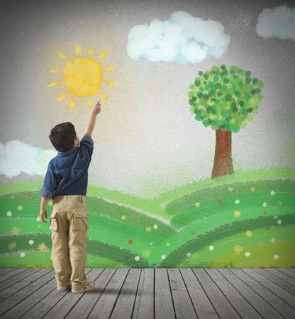 어린 아이는 회색 벽에 녹색 파노라마를 그립니다