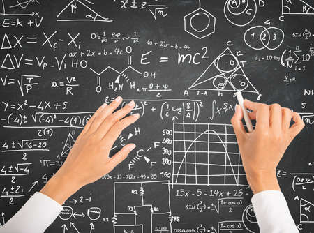 Hand writing science and math formulas on chalkboard photo