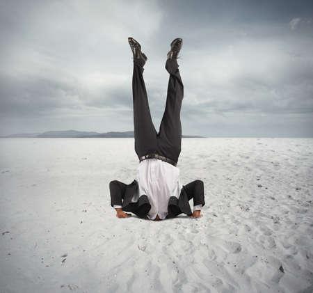 Concept van de economische neergang met zakenman op zijn kop Stockfoto